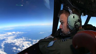 Flight Lieutenant Russell Adams looks out from the cockpit of a Royal Australian Air Force aircraft while searching for the missing plane.