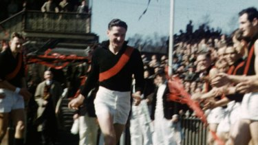 Essendon's Bill Hutchison runs through a guard of honour before the 1953 semi-final between Essendon and Footscray after winning the Brownlow Medal.