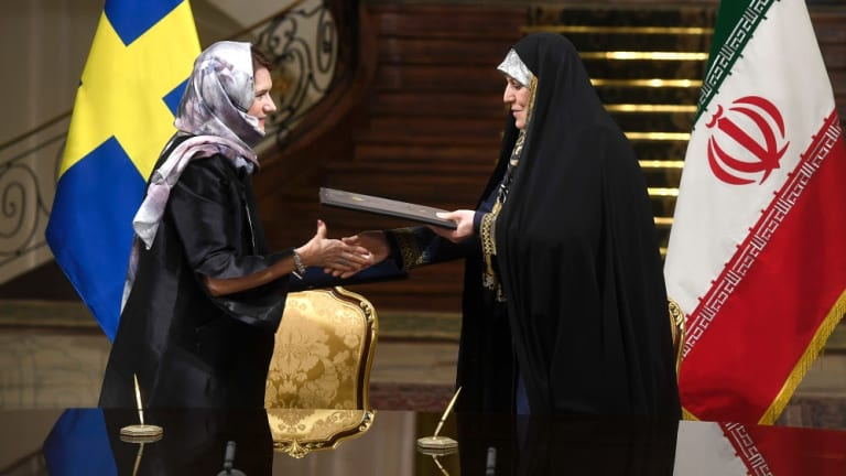 Sweden's feminist trade minister Ann Linde dons the hijab and wears a black cloak like her Iranian counterpart.