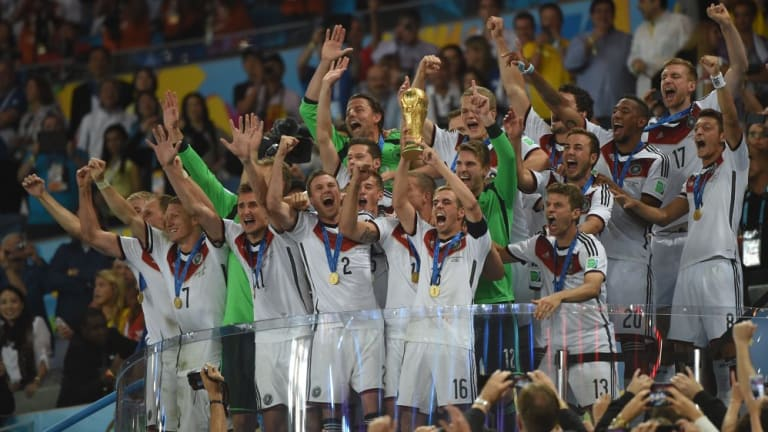 Germany's captain Philipp Lahm holds the trophy as the team celebrates winning its fourth World Cup.