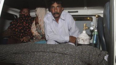 Grieving husband: Mohammad Iqbal, right, sits in an ambulance next to the body of his pregnant wife, Farzana Parveen.