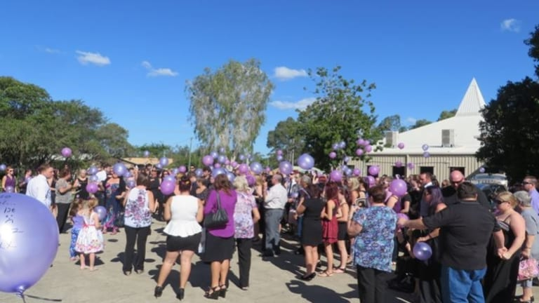 Mourners release purple balloons in memory of Talieha.