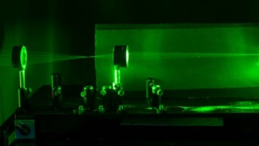 A laser shows the paths that light rays travel through the system, showing regions that can be used for cloaking an object.
