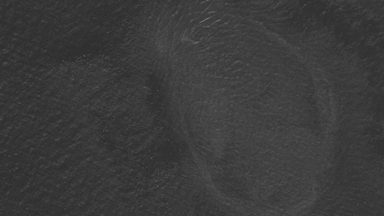 What some users say is a  oil streak in an oval formation with debris to the left of it.