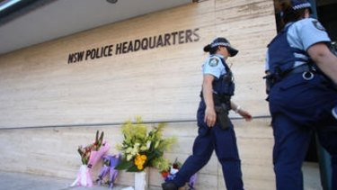 Police officers leave flowers outside police headquarters in Parramatta.