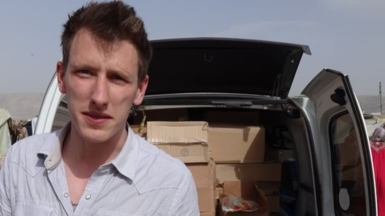 Peter Kassig standing in front of a truck filled with supplies for Syrian refugees. Islamic State militants later beheaded him.