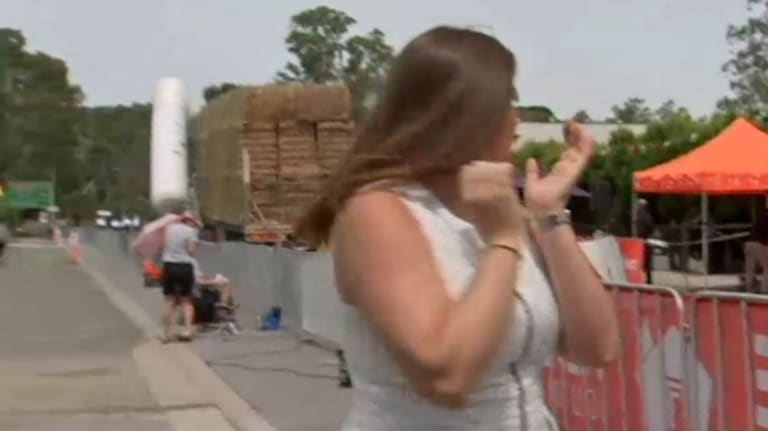 Reporter Sarah Hancock turns around as the truck begins to drag the inflatable structure.