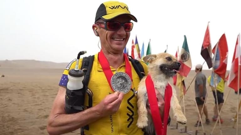 Gobi and Dion Leonard celebrate at the finish line.