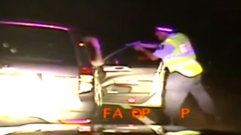 Footage shows the officer pointing the gun in the man's face as he climbs out and raises his hands in the air.