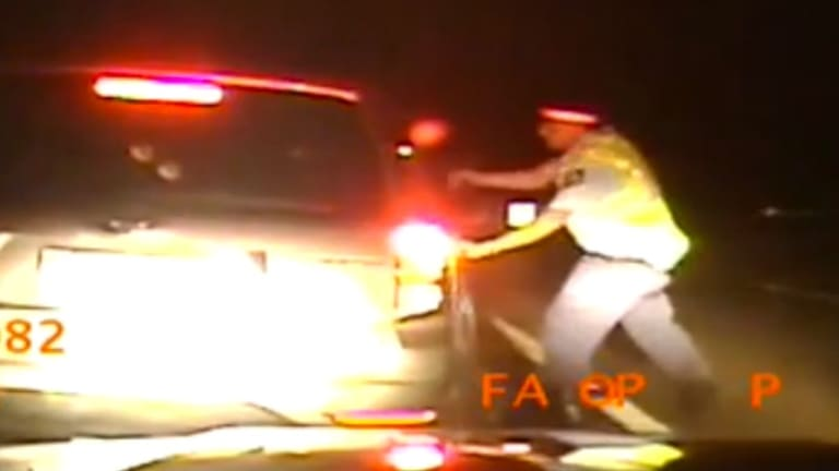 Police dash camera vision shows the officer running to the driver's side window with his gun drawn.