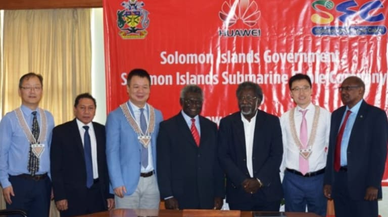 Solomon Islands Prime Minister Sogavare (centre) flanked by ministers and Huawei officials at a signing ceremony.