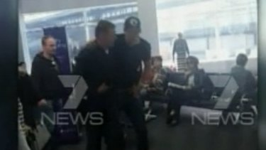 Grant Hackett is helped by a fellow passenger after the flight from Adelaide to Melbourne.
