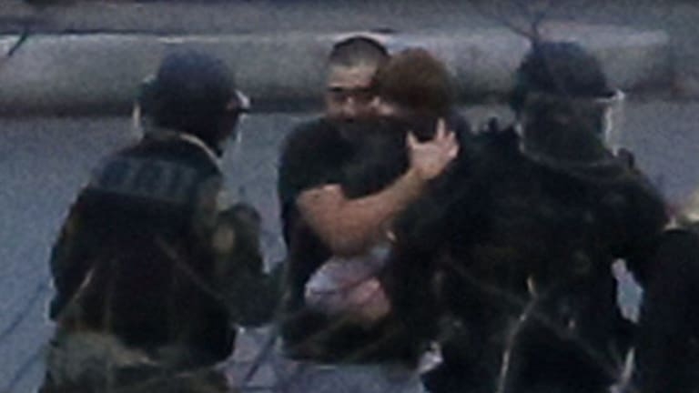 Hostages, including a small child, are led from the supermarket.