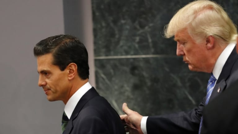 Donald Trump walks with Mexican President Enrique Pena Nieto, during a Presidential campaign visit.