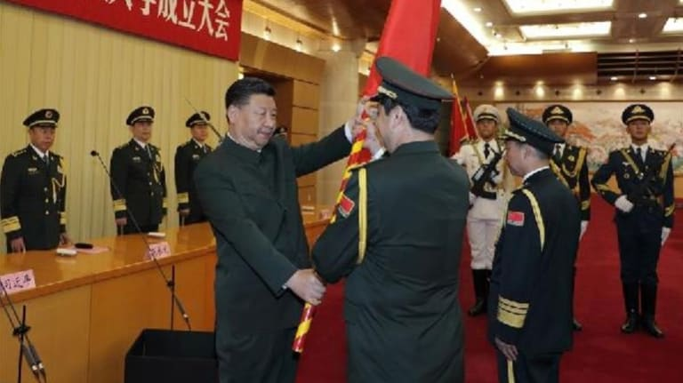 Xi Jinping hands the PLA flag to General Yang Xuejun after he was appointed head of the PLA Military Science Academy in July.
