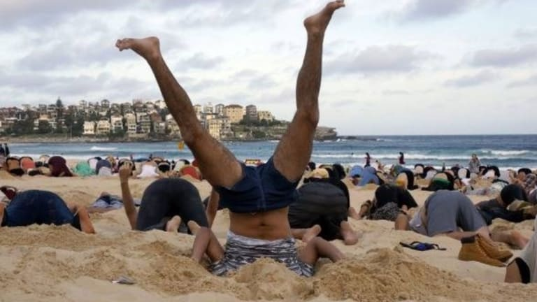 Australians bury their heads in the sands of Bondi Beach to send a message to Prime Minister Tony Abbott about the dangers of climate change.