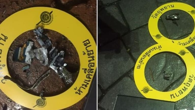 Bomb pieces marked as evidence at the scene.