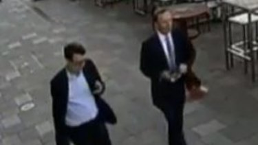 CCTV shows Tony Abbott, right, and one of his staffers walking in Hobart just before the assault.