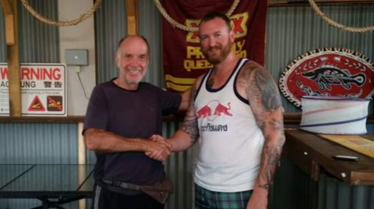 Geoff Keys thanks his rescuer, Senior Constable Brad Foat. Mr Keys was found after writing a plea for help in the sand in Jardine National Park.