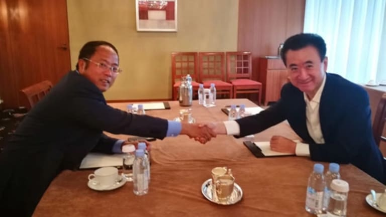 Huang Xiangmo, chairman of Yuhu Group, and entrepreneur Wang Jianlin of the Wanda group shake over the billion dollar deal.