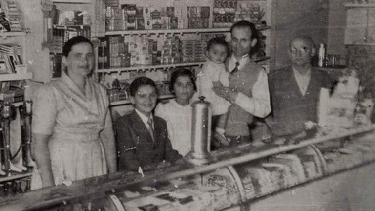 "George Poulos with his family behind the counter of The Rio in its golden years. From left, Stavroula, Nik, Aphrodite, George holding Margaret and George's father, Philip. ""We used to open until 11 o'clock waiting for the picture show to come out,"" says Nik Poulos."