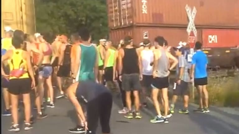 Runners were forced to stop and wait for the slow train to pass.