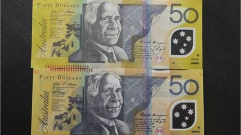 An image of a counterfeit $50 note (bottom) alongside a legitimate one.