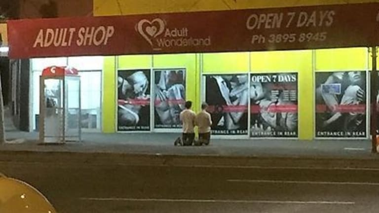 A photo posted on Reddit showing two men praying outside Annerley's Adult Wonderland last week.