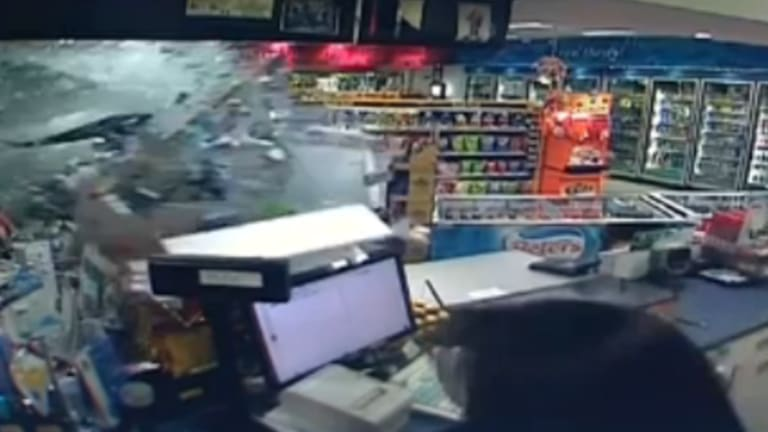 The Camry smashes through the side of the service station in Belfield.