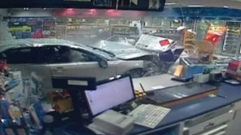 The car careens into goods within the shop.