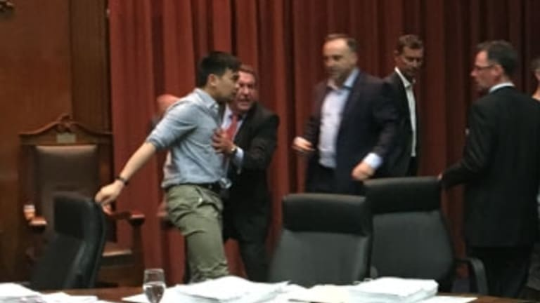 Councillor Nam Quach is helped to his feet after the meeting erupted into a brawl over parking meters.