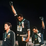 Australian Peter Norman (left) showed support for US athletes Tommie Smith, centre, and John Carlos as they stared downward during the playing of <i>The Star-Spangled Banner</I> at the 1968 Olympics.