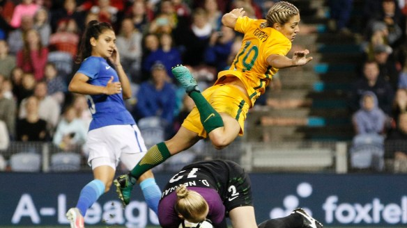 Leap of faith: Katrina Gorry dives over Brazil goalkeeper Daniele Neuhaus  during Tuesday night's international in Newcastle.