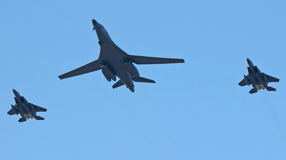 A nuclear-capable US B-1B bomber, centre, and two South Korean F-15K fighters fly over Seoul.