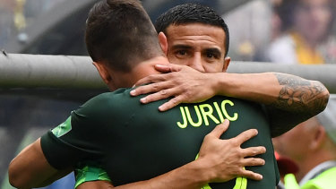 Cahill hugs Tom Juric as his teammate enters the game against Denmark.