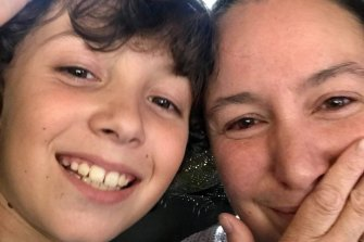 Jen Clark with her eight-year-old son Kai who spent the night in the library of his school due to floodwaters.