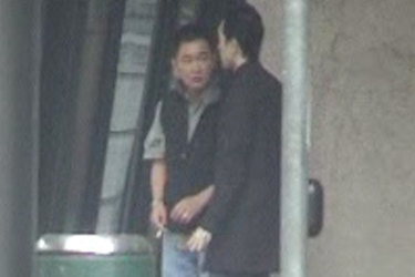Shore party member Teng (left) with another man waiting in central Melbourne and captured on surveillance footage.
