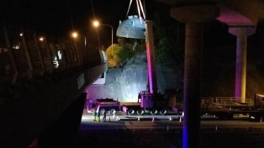 A crane was used to free thetruck and its load from the M1 Pacific Motorway off-ramp.