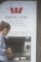 Mr Woodman's assistant takes cash out of an ATM.