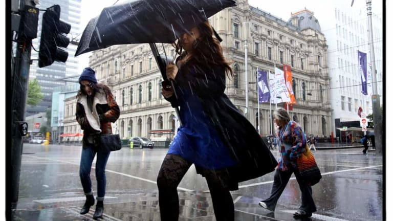 Rain and wind batter Melbourne as shoppers try to take cover on Elizabeth Street.