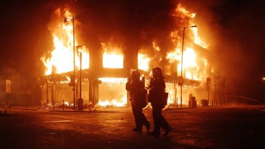 Police look on as fire rages through a building in Tottenham, north London Sunday, Aug. 7, 2011.