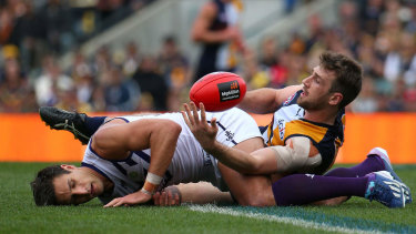 Eric Mackenzie of the Eagles tackles Matthew Pavlich of the Dockers after a marking contest.