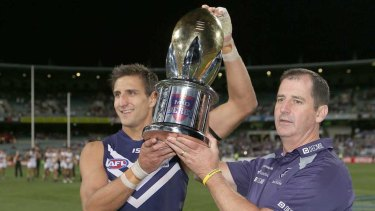 Matthew Pavlich and coach Ross Lyon hold the western derby trophy after defeating West Coast in 2013.