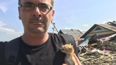 Correspondent James Massola holds kitten he rescued from a house in Petobo, Indonesia.