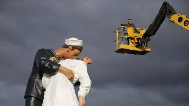 """A worker takes a picture of the """"Unconditional Surrender"""" sculpture by artist Seward Johnson during its installation outside the Memorial of Caen museum in Caen."""