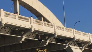 Extinction Rebellion protester Sean Nolan, 35, has been suspended from a rope on the William Jolly Bridge.