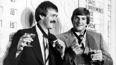 Bernie Quinlan (Fitzroy) and Barry Round, captain of South Melbourne, toast their Brownlow Medal win in 1981 .