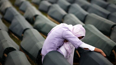 A Muslim woman prays beside the coffin of her relative, one of 534 victims of the 1995 Srebrenica massacre lined up for a joint burial in Potocari in 2009.