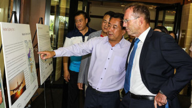 Jack Lam looks on as Tommy Jiang explains the multimillion-dollar redevelopment of the Twin Creeks Golf Club to Tony Abbott last year.