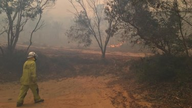 A firefighter at Happy Valley on Monday night as bushfire threatened the small township on the east coast of Fraser Island (K'gari).